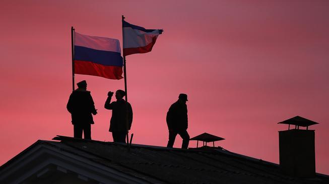 Muži připevňují ruskou vlajku na střechu radnice v krymském městě Bachčisaraj