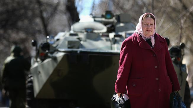 Stará žena v Simferopolu, za ní ruský tank