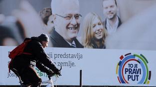Z chorvatské volební kampaně: cyklista před billboardem stávajícího prezidenta Iva Josipoviče