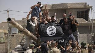 Iráčtí vojáci se na památku fotí se strženou vlajkou Islámského státu