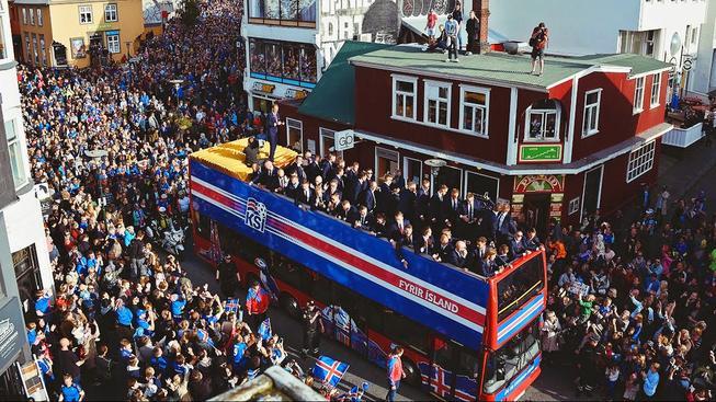 Islandský tým na střeše autobusu v zaplněných ulicích Reykjavíku