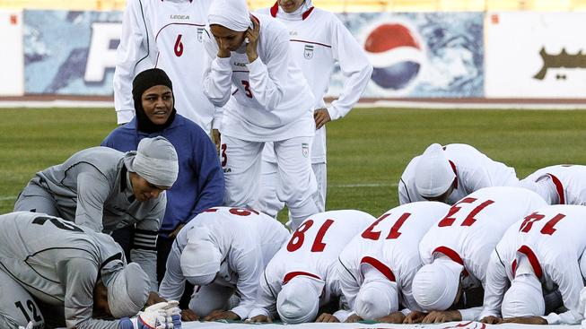 Íránský tým fotbalistek se modlí před zápasem k Alláhovi. Podobnou cestou se vydaly i hráčky Jordánska