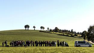 Migranti v doprovodu policejního auta pochodují do bavorské vesničky k první registrační stanici po překročení německých hranic