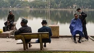 Pohled na práci pouličního holiče není v Hanoji vůbec vzácný