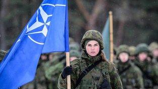 Vojenské cvičení NATO v Litvě, vojačka s alianční vlajkou. Ilustrační snímek