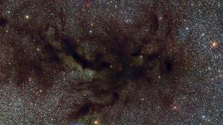 Tmavá mlhovina Dýmka, jejíž prach pohlcuje světlo hvězd v pozadí