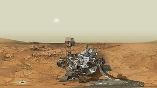 Složený autoportrét sondy Curiosity uprostřed marsovské pustiny, vlevo otvor po vrtání palubním laserem