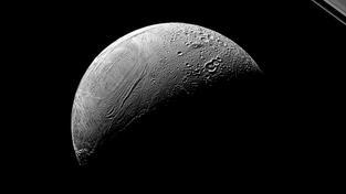 Na povrchu maličkého, ale velmi aktivního měsíce Enceladu vidíme starší hustě kráterovaný terén i mladý terén pokrytý trhlinami. Vpravo nahoře jsou v pozadí vidět prstence Saturnu. Snímek byl pořízen sondou Cassini v srpnu 2015