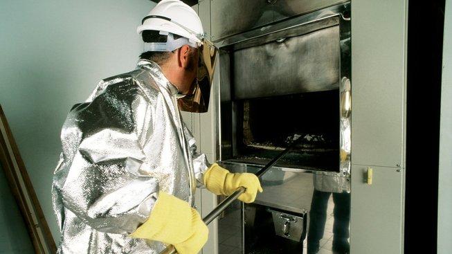 Pracovník krematoria vytahuje popel z pece