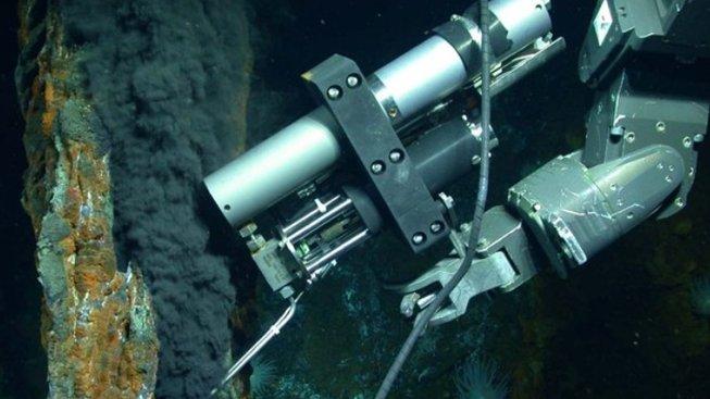 Dálkově ovládaná robotická ruka sbírá vzorek z hydrotermálního otvoru v hornině