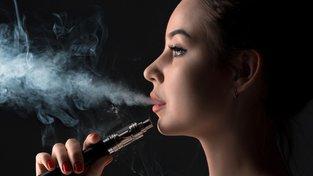 Dívka vydechuje kouř z elektronické cigarety