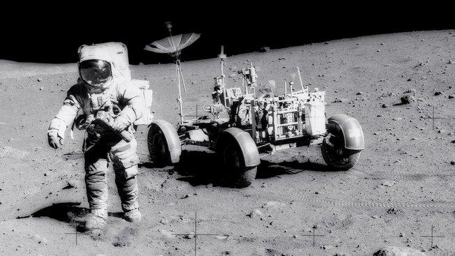 Astronaut Scott, člen mise Apollo 15, jde po Měsíci. V pozadí je vidět lunární vozík. Od této chvíle uběhlo už dlouhých 48 let