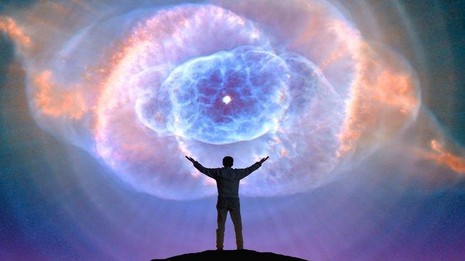 Muž stojící pod umírající hvězdou obklopenou mračny plynu a prachu
