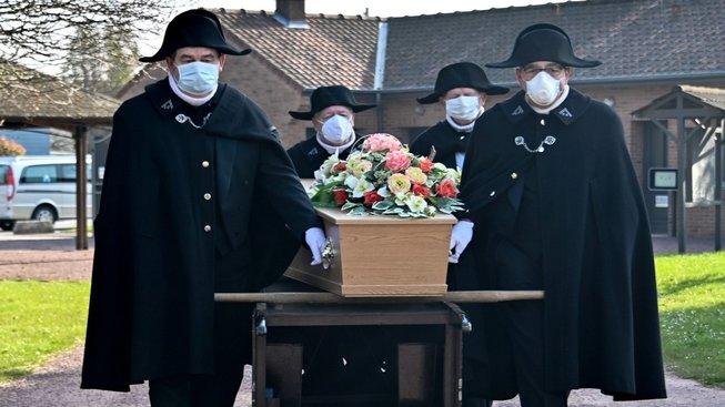 Členové dobročinného bratrstva Saint-Eloi vezou rakev s obětí koronaviru na hřbitov ve francouzské obci Bethune