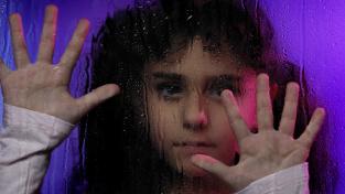 Osamělá holčička za sklem.