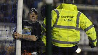 A man (L) handcuffs himself to the goal post during the Premier League match between Everton and Manchester City in Liverpool, January 31, 2012. REUTERS/Nigel Roddis
