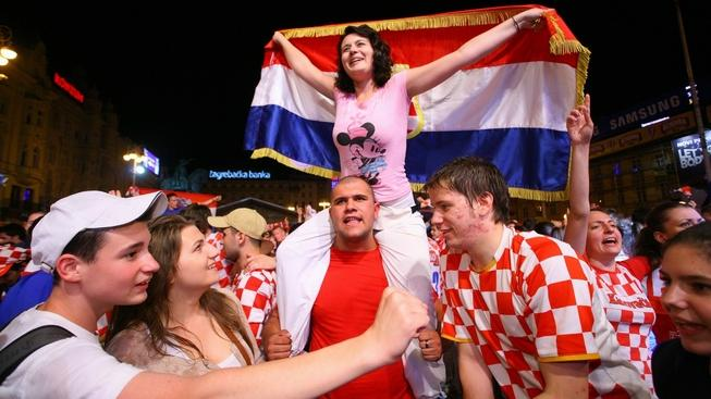 Image: 0131211865, License: Rights managed, Croatian football fans celebrate at Zagrebs main square on June 10, 2012 after their squad defeated Ireland 3-1 in their first victory at Euro 2012, seen here as a key match paving the way to reach the championship quarter-finals.  More than 1,000 people gathered at the capital Zagreb's main square to watch on a giant screen, erected at an improvised stage, live broadcast of the match played in Poznan, Poland.   AFP/str, Place: CROATIA, Model Release: No or not aplicable, Credit line: Profimedia.cz, AFP