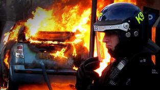 Policista smutní vedle hořícího auta.