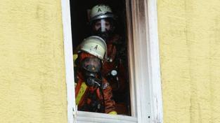 Požárníci v hořícím objektu ve městě Backnang.