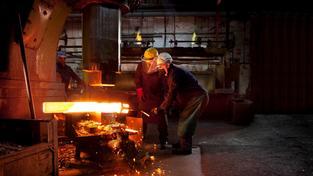 Fotka dvou pracujících dělníků při práci s roztaveným kovem