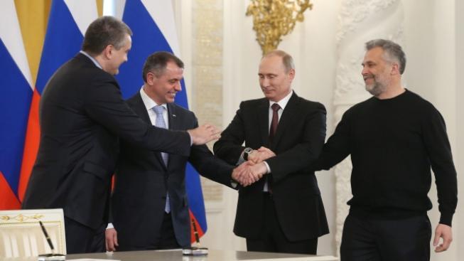 Ruský prezident Vladimir Putin se zástupci separatistické vlády Krymu po podepsání dohody o přidružení.