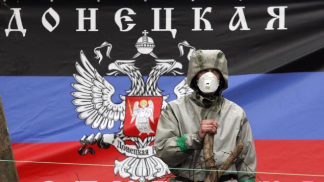 Proruský separatista stojí před vlajkou 'Doněcké republiky'