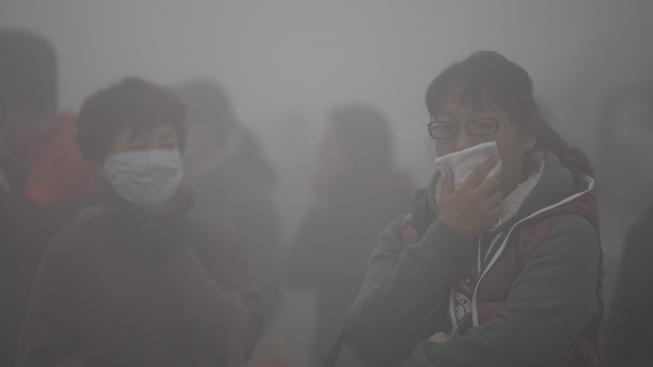Lidé v Pekingu jsou neustále obklopeni hustým smogem (ilustrační foto)