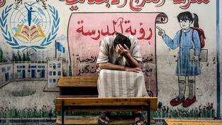 Palestinec před školou provozovanou OSN v pásmu Gazy