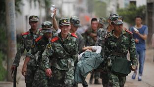 Záchranáři transportují zraněné v Čao-tchungu