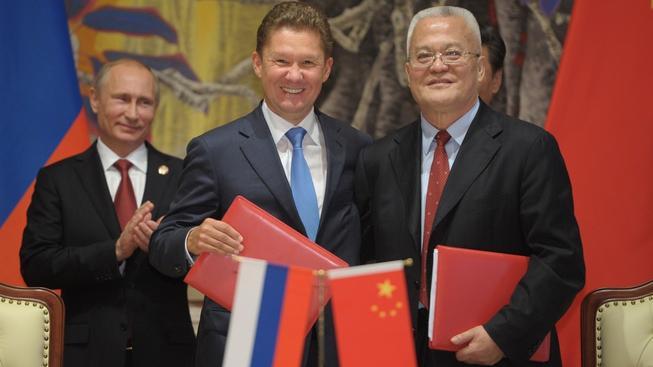 Šéfové Gazpromu a CNPC při podepsání rámcové dohody během květnové návštěvy Číny ruského prezidenta Vladimira Putina (v pozadí)