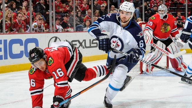 Útočník Winnipegu Michael Frolík (v bílém) si připsal na ledě Chicaga první gól v sezoně