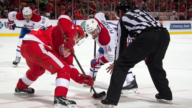 Tomáš Plekanec (v bílém) při buly v utkání na ledě Detroitu
