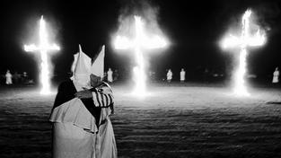 Členové Ku Klux Klanu se symbolickými hořícími kříži v pozadí
