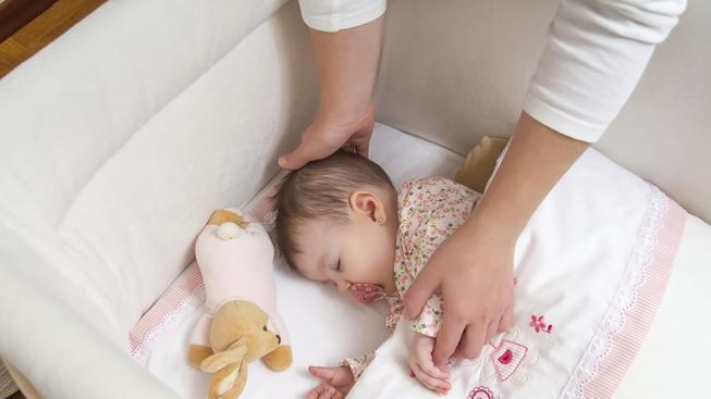 Rodiče děti občas přikrývají, protože se bojí, aby jim nebyla v noci zima. Správně by však dítě mělo být v postýlce samo, bez peřiny a spát na zádech.