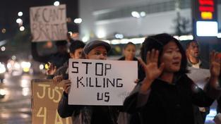 Přestaňte nás zabíjet, hlásá jeden z transparentů na protipolicejních demonstracích