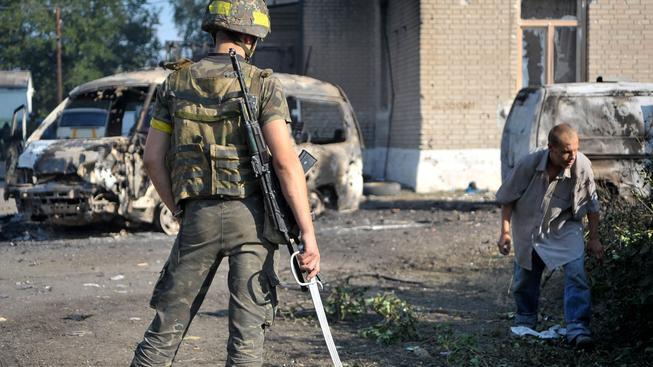 Ukrajinský voják dohlíží na zajatého proruského ozbrojence, který uklízí základnu v Ilovajsku asi 50 km od Doněcku