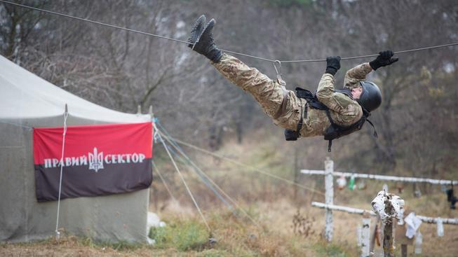 Vojenský výcvikový tábor pro civilisty poblíž Kijeva s vlajkou Pravého sektoru v pozadí