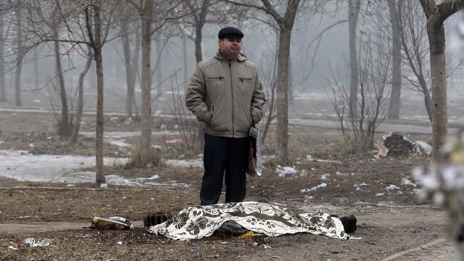 Muž pláče nad jednou z obětí bombardování Mariupolu 24. ledna, při němž zemřelo 30 lidí