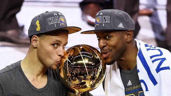 Stephen Curry (vlevo) a Andre Iguodala se mazlí s pohárem pro vítěze NBA