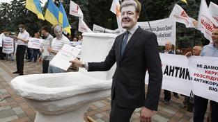 Protest proti korupci v ukrajinské vládě. Demonstrant s maskou Porošenka splachuje kriminální složky v maketě toalety
