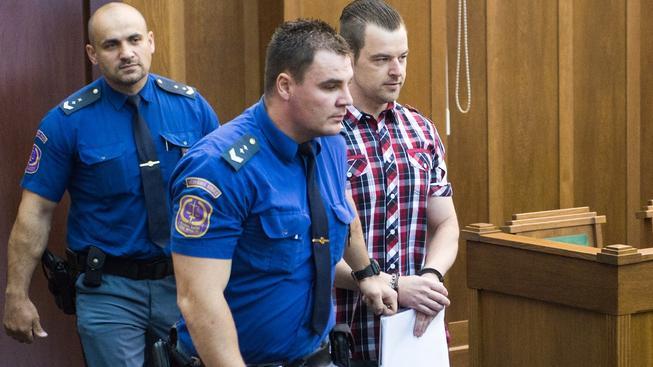 Petr Kramný vstupuje do soudní síně v doprovodu vězeňské služby