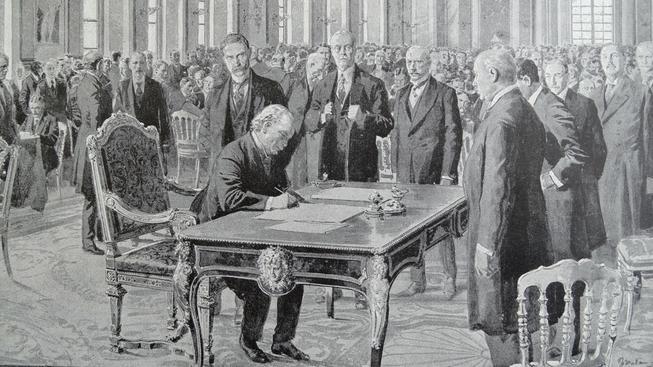 Britský premiér David Lloyd George podepisuje Versailleskou smlouvu