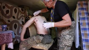 Dobrovolná zdravotnice ošetřuje ukrajinského vojáka