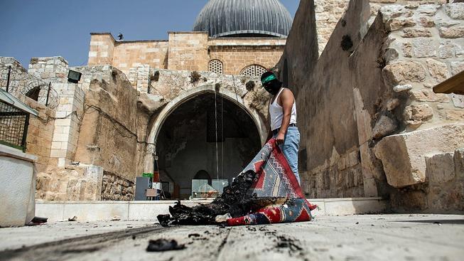 Nepokoje u mešity Al-Aksá nepropukly poprvé. Na snímku maskovaný Palestinec s čelenkou Hamasu vynáší z mešity spálený koberec
