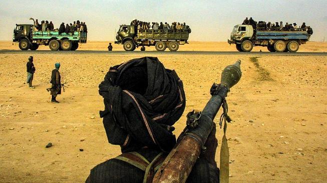 Archivní fotka z 28. listopadu 2001. Bojovníci Severní aliance se dívají na transport zajatých Talibanců z Kundúzu do Mazár-e Šarífu
