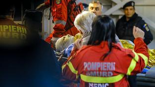 Záchranáři nakládají jednoho ze zraněných do sanity