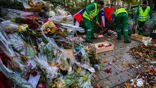 Úklidová četa sklízí květiny před klubem Bataclan