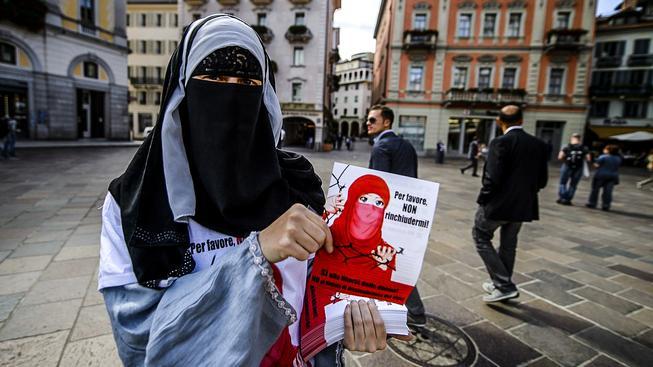 Jedna z mála Švýcarek nosících nikáb s letáky, na kterých stojí 'Prosím, nezavírejte mě'