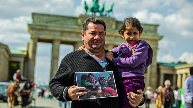 Laith Majid s dcerkou drží v ruce fotografii, která mu změnila život a změnila i pohled na uprchlíky