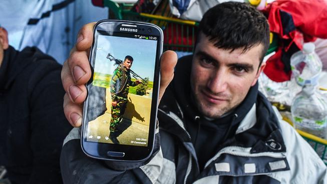 Kurdský uprchlík ukazuje fotografii sebe jako  pešmergského bojovníka. Ilustrační snímek